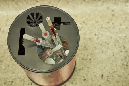 Used needles and cap, broken glass of used drug in container of biohazard disposal in opeerating room Stock Photo