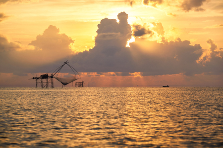 Scene of giant net fishing or Yor, a fisherman on longtail boat and crepuscular ray