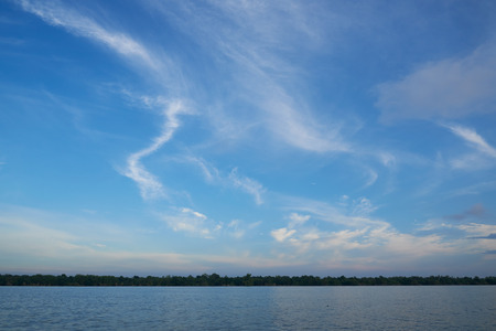 Beautiful cirrus clouds over the sea on blue sky background Stock Photo