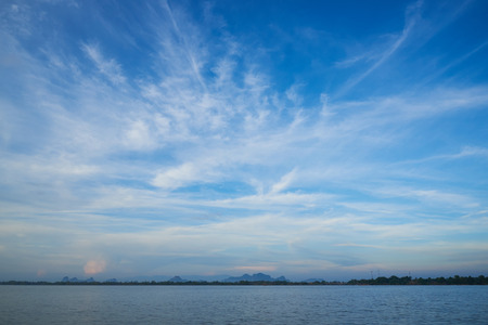 Beautiful cirrus clouds over the sea and blue sky background