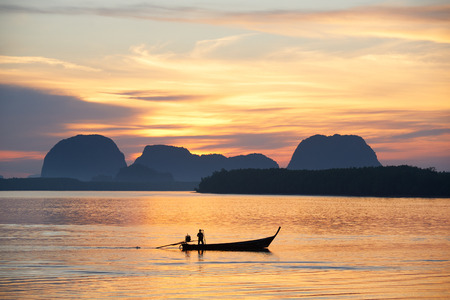 Silhouette image of a fisherman on longtail boat against sunrise behind the mountain background