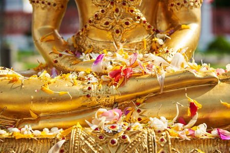 Flowers on Buddha statue after pouring water in Thai new year day or songkarn festival Stock Photo