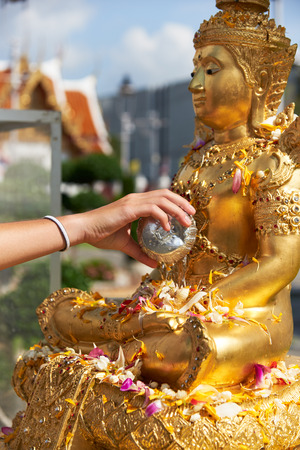 Tourist hand pouring water to bath Buddha statue in Thai new year day or Songkarn festival Stock Photo