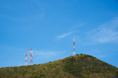 Telephone attennas on the mountain against blue sky background