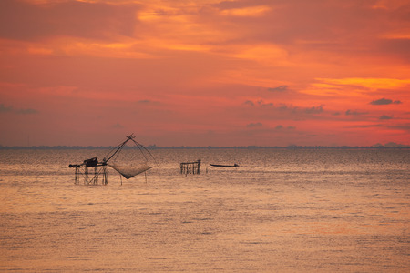 A giant square net fishing and silhouette of a fisherman on longtail boat agianst orange sky background Stock Photo