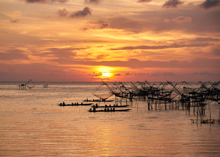 Silhouette image of tourists on the long tail boat taking photography of Yor, fishing net of fishermen, during sunrise in the morning at Pakpra, Phatthalung, Thailand.