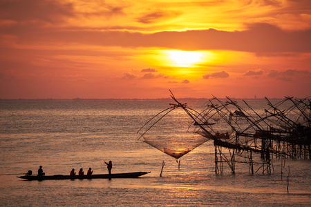 Tourists on the long tail boat taking photography of Yor, net fishing of fishermen, during sunrise in the morning at Pakpra, Phatthalung, Thailand. Stock Photo