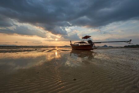 Scene of longtail boat on the beach and texture of sand during sunset at Krabi province, Thailand Standard-Bild