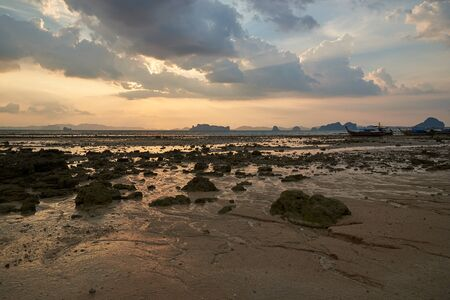 Scene of sunset at the beach during low tide at Krabi province