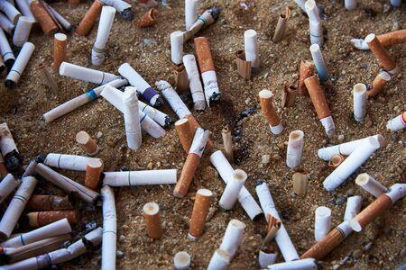 Many cigarette butts closed in the sand ashtray Standard-Bild