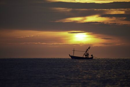 Silhouette of a fisherman on longtail boat with sunrise and beautiful color sky