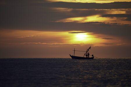 Silhouette d'un pêcheur sur bateau longtail avec lever de soleil et beau ciel de couleur