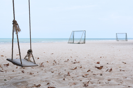A wooden swing and soccer goal on the beach and blue sky background