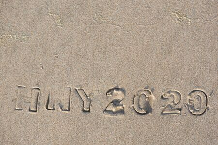 Happy new year 2020. Imprinted texts and alphabets  on the beach