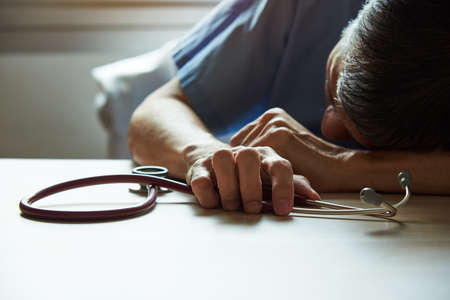 An asian burnout surgeon feeling tired in medical office with a stethoscope on the table