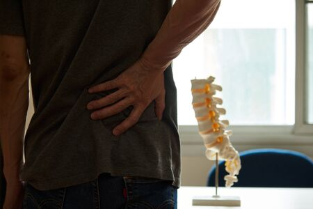 A male patient visiting medical clinic for low back pain. Lumbar vertebral model on doctor desk.