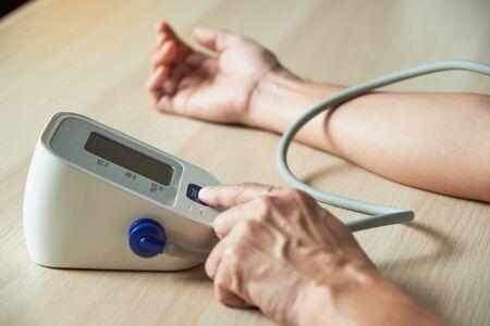 Close-up view of self measurement blood pressure using finger pressing digital sphygmomanometer