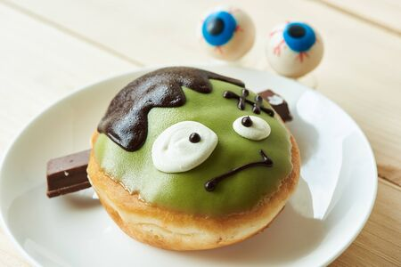 A delicious cute green doughnut in ghost face on the plate. Eyeballs on wooden table in background.