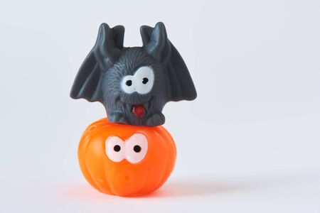 Happy Halloween. A bat on the top of orange pumpkin on white background