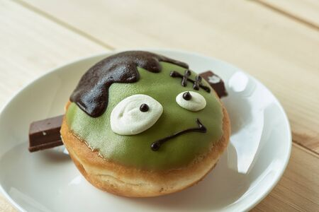 A cute delicious green doughnut in ghost face on wooden table.