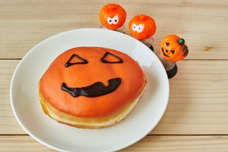 A plate of delicious halloween doughnut on wooden table. 写真素材