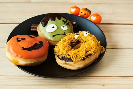 A plate of delicious halloween doughnut on wooden background 写真素材