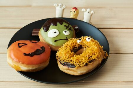 A plate of three tasty halloween doughnut on wooden background 写真素材
