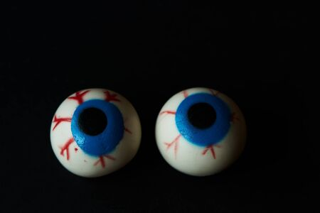 Two hallloween scary eyeballs on black background