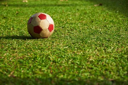 An old red football on the green grass in a sunny day