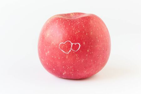 A tasty, heart painting on red apple on white background with clipping path Imagens