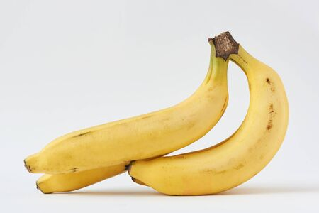 A bunch of tasty cavendish bananas on white background Imagens