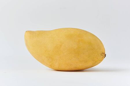 A tasty ripe yellow mango on white background