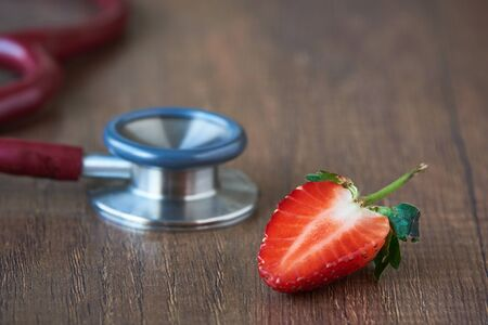 Concept of eating strawberry and good health. A half of strawberry and red stethoscope on wooden background. Imagens
