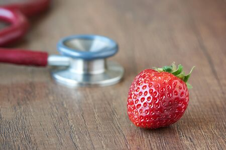 Concept of eating strawberry and good health. A strawberry and red stethoscope on wooden background. Imagens