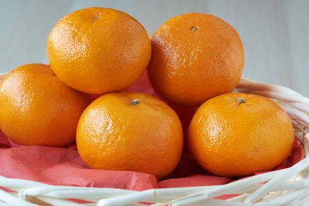 A group of tasty mandarin oranges in the basket on wooden background. A gift for Chinese new year. Imagens