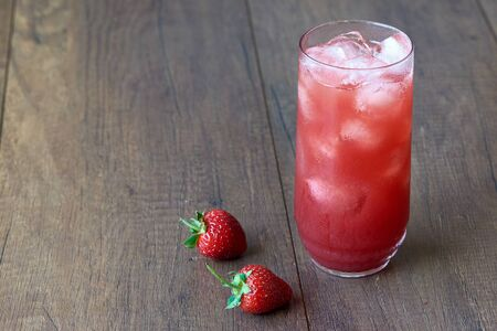 A glass of tasty cold strawberry juice with ice on the table. Delicious red strawberries on wooden background