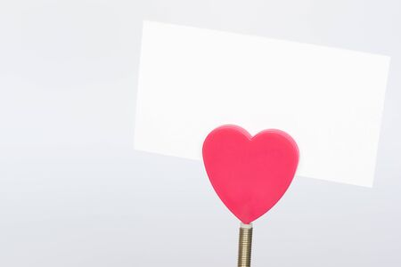A red heart shape paper holder and a white paper on white background