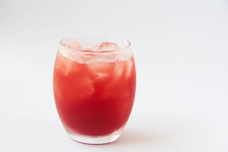 A glass of tasty cold strawberry juice with ice on the table.  Imagens