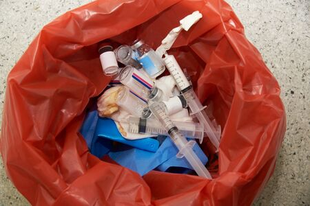 Used bottles of medications, gauzes, syringe and surgical gloves in a red garbage bin in operating room Imagens