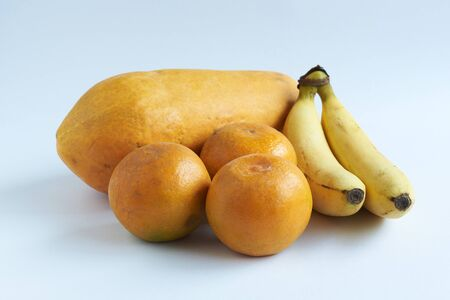 Oranges, bananas and papaya on white background Imagens