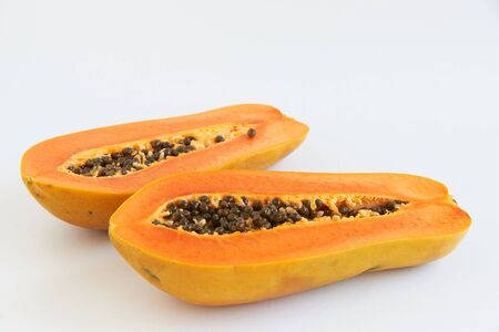 Two of delicious half cut papayas and seeds on white background