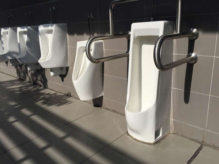 Row of white  ceramic urinal in public restroom and morning sunlight