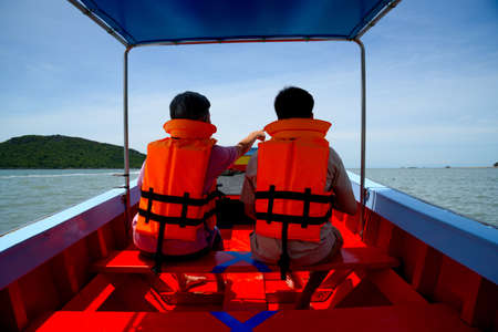Two Asian tourists wearing life jacket on longtail boat with social distancing maker at the seats