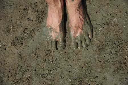 A man showing mud feet after walking on the beach during low tide
