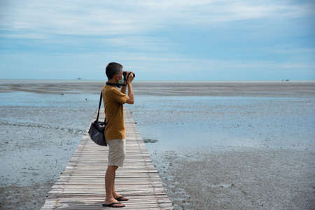 A senior Asian male wearing face mask taking photographat low tide sea  on the wooden foot path