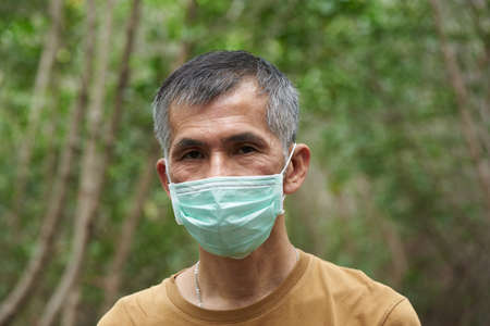 Image of a senior Asian male wearing face mask while travelling during coronavirus outbreak