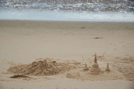 Forming beach sand as Buddhist temples on the beach. Using seashells to be towers.