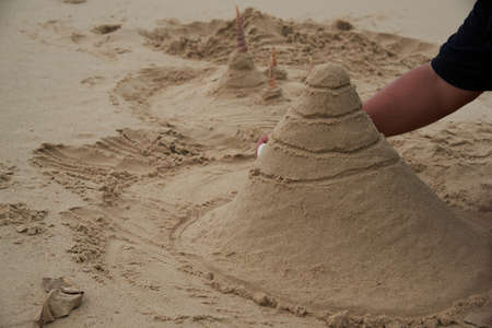 Making Buddhist temples form sand on the beach. Using seashells to be towers.