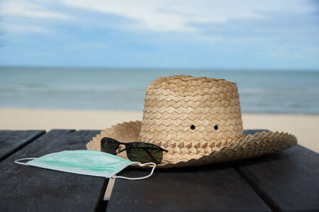 Concepts of taking vacation during coronavirus outbreak. Face mask, sunglasses and hat on wooden table. Background of beautiful beach and blue sky.