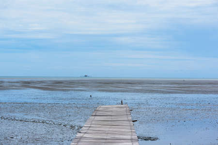 Wooden walk way and sea shore on blue sky background during low tide at The Leam Phak Bia environmental study and  development project at Phetchaburi, Thailand Stockfoto